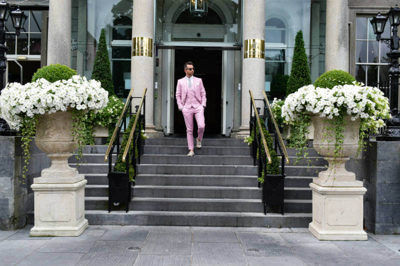 Walking down steps in a Pink Suit